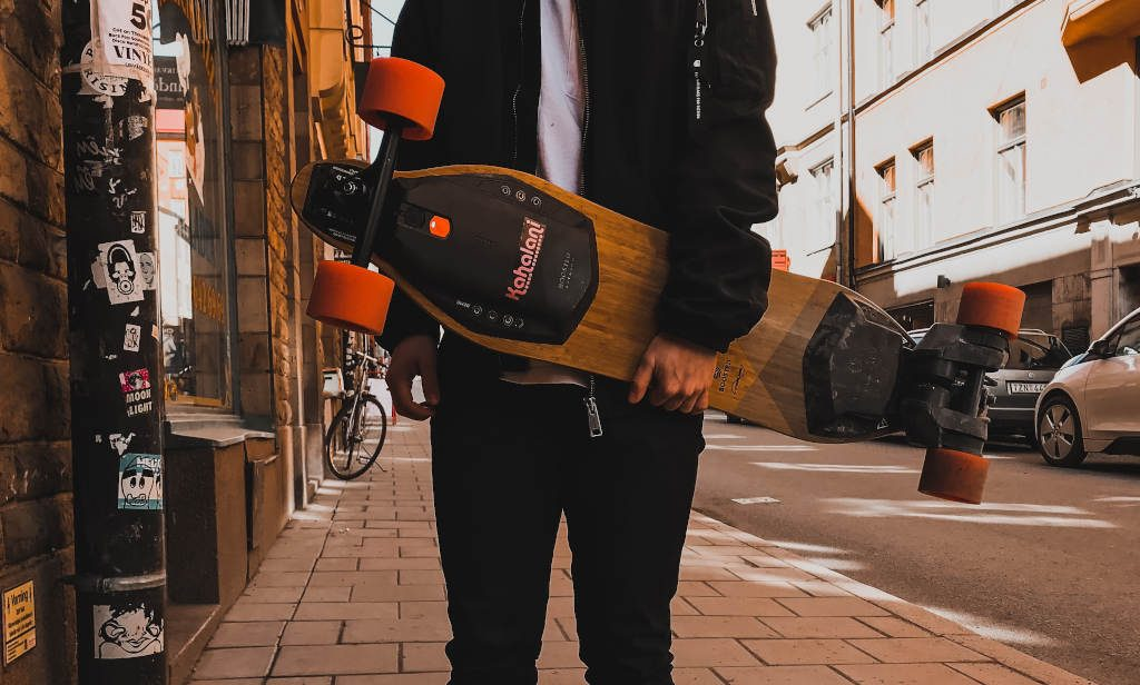 Boy holding the electric skateboard