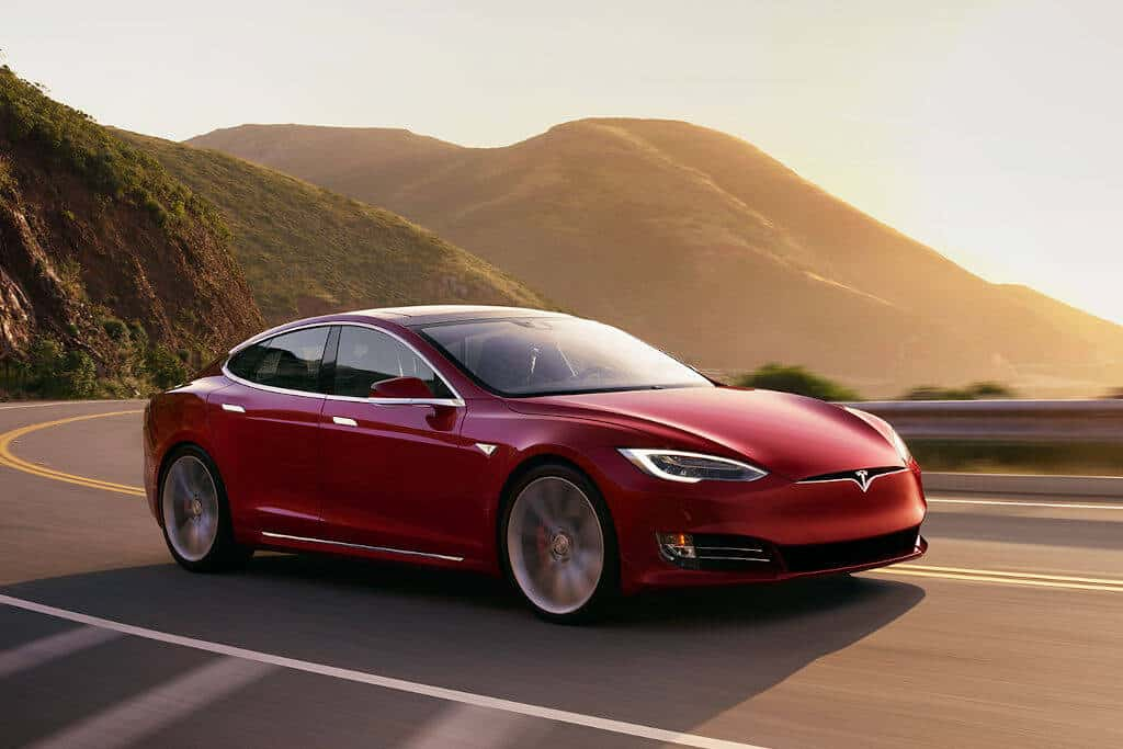 Tesla Model S in motion at red sunset